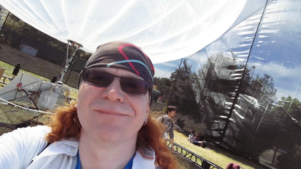 Chris Heilmann covered in sunscreen, wearing a bandana in front of Google Loon